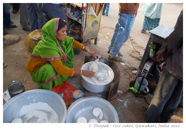 Woman cooking rice cakes on roadside, Guwahati, Assam, India
