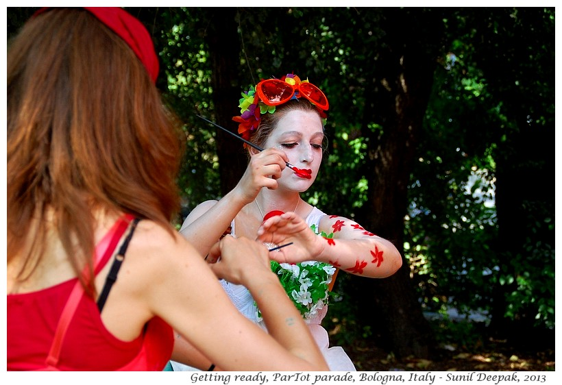 Girl painting red flowers on her body, Par Tot parade, Bologna, Italy - Images by Sunil Deepak